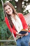 Teenager reading a book. A beautiful teenager sitting on a hammock reading a book Stock Images