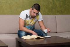 Teenager Reading A Book In Cafe. Young Male Student Drinking And Reading Book In Cafeteria Stock Photos