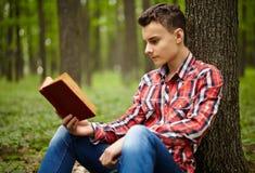 Teenager reading a book Stock Photos