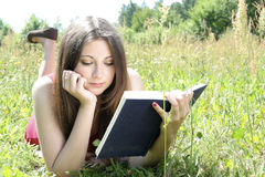 Teenager reading book in field. Attractive young female teenager reading book in countryside field or meadow Stock Image
