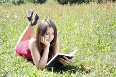 Teenager reading book in field Royalty Free Stock Photos