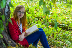 Teenager reading a book in forest. Teenager in glasses and in red jacket sitting in forest and reading a book stock image