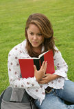 Teenager reading book on grass Royalty Free Stock Images