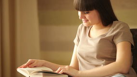 Teenager reading book and looking away stock footage