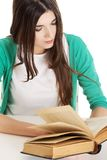 Teenager reading book. Pretty teenager reading interesting book Royalty Free Stock Photography