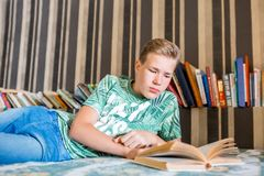 The teenager is reading a book. Selective focus. The teenager is reading a book Selective focus Royalty Free Stock Photo