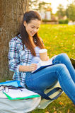 Teenager reading book with take away coffee Stock Images