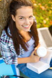 Teenager reading book with take away coffee. Education, campus and people concept - smiling teenager reading book with take away coffee Stock Photos