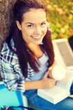 Teenager reading book with take away coffee Royalty Free Stock Image
