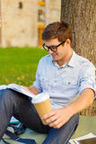 Teenager reading book with take away coffee. Education, campus and people concept - smiling teenager in eyeglasses reading book with take away coffee Stock Image