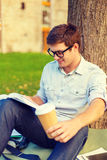 Teenager reading book with take away coffee Royalty Free Stock Photo