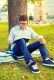 Teenager reading book with take away coffee Royalty Free Stock Images
