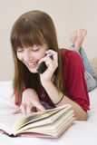 Teenager reading book and talking on a phone Royalty Free Stock Images