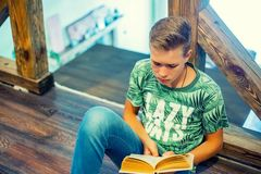 The teenager is reading a book. Top view. Selective focus. Stock Photos