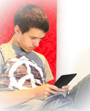 Teenager reading an eBook. A teenage boy educating himself reading a book on an elecronic ebook reader Stock Images