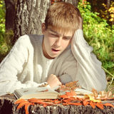 Teenager reading outdoor. Toned photo of Teenage Boy sit in the Autumn Forest with a Book Stock Photography