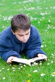 Teenager reading outdoors Royalty Free Stock Images