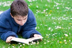 Teenager reading outdoors Stock Image