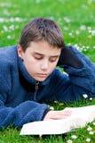Teenager reading outdoors Stock Photos
