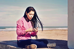 Teenager reading a text in her cell. Teenager sitting in the beach with her cellphone in hands and reading a text  in Mar del Plata, Argentina Stock Images