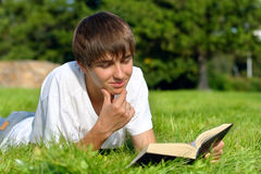Teenager reads book. The teenager reads the book on a summer meadow Stock Image