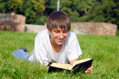 Teenager reads book. The teenager reads the book on a summer meadow Stock Images
