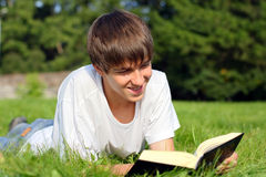 Teenager reads book. The teenager reads the book on a summer meadow Stock Photography