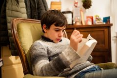 Teenager reads a book on the armchair at home. At evening light Royalty Free Stock Images