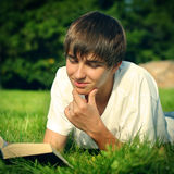 Teenager reads a Book. Toned photo of Teenager reads the book on a Summer Lawn Stock Photo