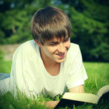 Teenager reads a Book. Vintage photo of Teenager reads the Book on a Summer Meadow Royalty Free Stock Photos
