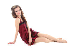Teenager in red dress sitting over white Royalty Free Stock Photography
