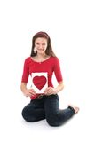 Teenager and red heart. Teenager girl with red shirt holding a board with heart Stock Photo
