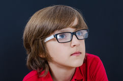 Teenager in red polo shirt and glasses is looking up Royalty Free Stock Images