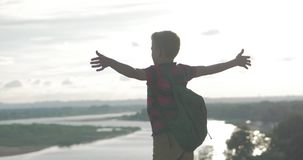 Teenager in a red shirt with a backpack on his back, at sunset, sitting on a high hill and looking at the clouds in the