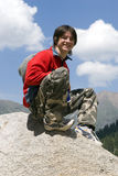 Teenager in red sport pullover in mountain. Hike and blue sky Stock Image