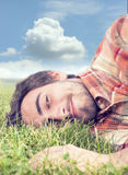 The teenager relaxes. Happy teenager laying down in the grass and looks up to sky Stock Photos
