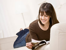 Teenager relaxing on sofa reading magazine Stock Photography