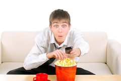 Teenager with remote control. Amazed teenager with remote control and popcorn Stock Image