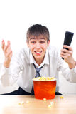 Teenager with remote control. And popcorn Royalty Free Stock Images