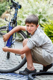 Teenager repairing his bike, changing broken tyre Royalty Free Stock Images
