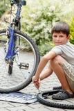 Teenager repairing his bike, changing broken tyre Stock Photo