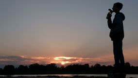 Silhouette of a boy riding a self-balancing two-wheeled gyro scooter. A teenager rides on the waterfront and drinks stock video