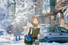 Teenager riding bicycle. Portrait of little boy riding bicycle on snowy street royalty free stock photo