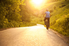 Teenager riding a bicycle on the road summer sunlit stock image