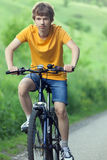 Teenager riding a bicycle on the road summer sunlit.  Stock Photography