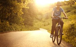 Teenager riding a bicycle on the road summer sunlit. Bike ride stock photos