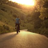 Teenager riding a bicycle on the road summer sunlit. Bike ride royalty free stock photography