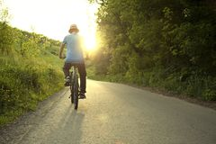 Teenager riding a bicycle on the road summer sunlit. Bike ride Stock Photography