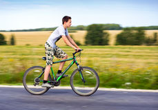 Teenager riding a bike Royalty Free Stock Image