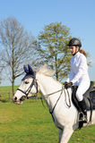 Teenager riding horse. Side view of teenage girl riding white horse in countryside Stock Photography